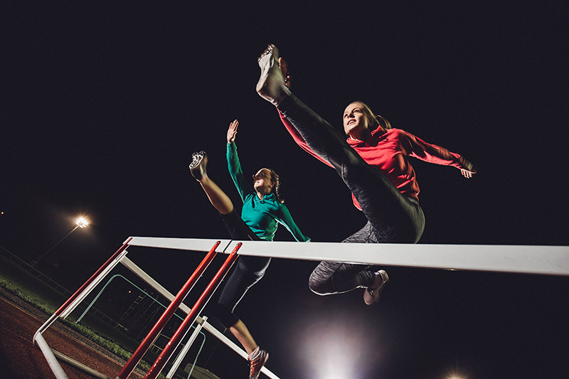 Two women jumping over hurdles